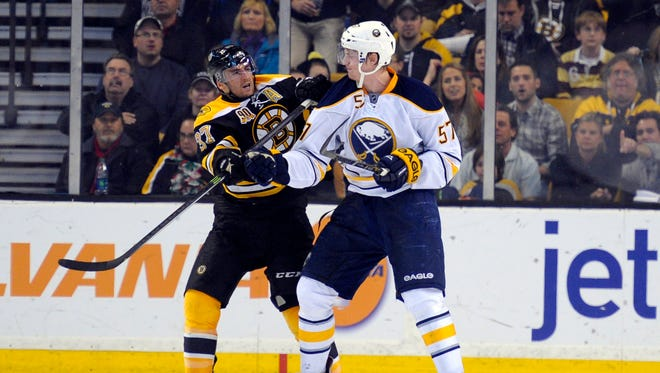 Boston Bruins center Patrice Bergeron (37) crosschecks Buffalo Sabres defenseman Tyler Myers (57) during the second period.