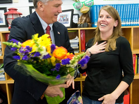 Santa Rosa County School District Superintendent, Tim Wyrosdick, left, names Holley-Navarre Intermediate fourth-grader teacher, Danielle Clark, right, as the district's 2015 Teacher of the Year during a ceremony Friday morning Feb. 7, 2014.