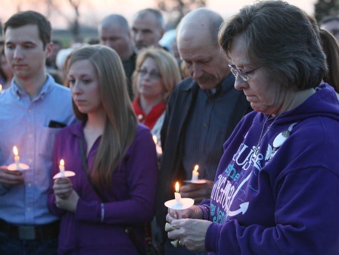 Leannda Bruck, right, stands with family during a vigil
