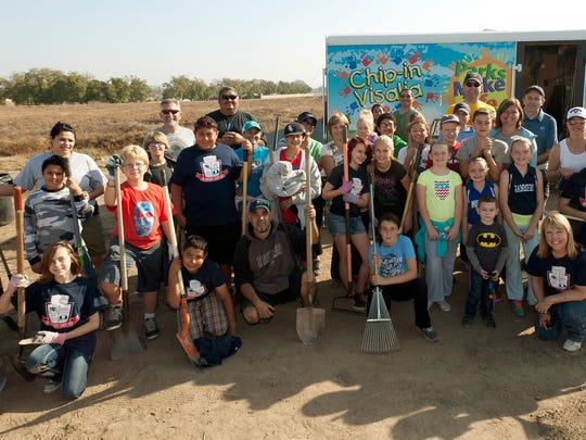A group from Oak Grove Elementary School poses for pictures after helping plant 700 trees and plants along the St. Johns River in Visalia for Make A Difference Day in Visalia on October 26, 2013.