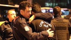Police officers hug each other after an explosion around