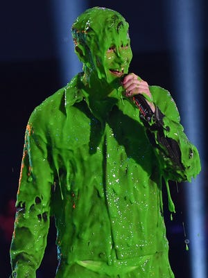 Singer Nick Jonas get slimed while accepting the award for Favorite Male Singer onstage during Nickelodeon's 28th Annual Kids' Choice Awards on March 28, 2015.