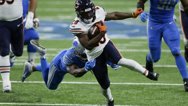 Chicago Bears running back Tarik Cohen (29) tries to break the tackle of Detroit Lions strong safety Duron Harmon (26) in the first half of an NFL football game in Detroit, Sunday, Sept. 13, 2020.