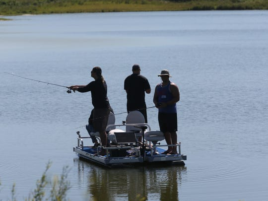 Fishermen cast lines in a farm pond outside Williamsburg, Iowa, in this file photo from July 2014.  New rules issued by the EPA and Department of the Army are aimed at clarifying  federal jurisdiction over bodies of water.