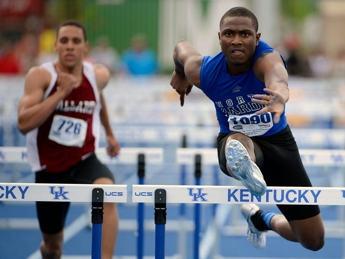 Dante Johnson of North Hardin clears a hurdle next to Ballard's Terran Meek to finish first in the Boys 110 Meter Hurdles during the KHSAA 3A Track and Field finals at the University of Kentucky.  (Photo by Jamie Rhodes, Special to the Courier-Journal)  May 24, 2014