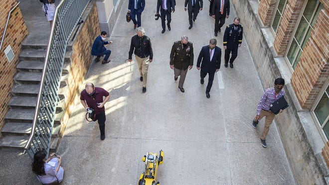 A robot leads U.S. Army Secretary Ryan McCarthy, Gov. Greg Abbott, University of Texas President Jay Hartzell and others Friday on a tour of a robotics lab at UT built in collaboration with the Austin-based Army Futures Command.