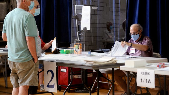 Tom Travers, right, election warden at the Fairbank Community Center in Sudbury, checks in voters during Tuesday's town election.