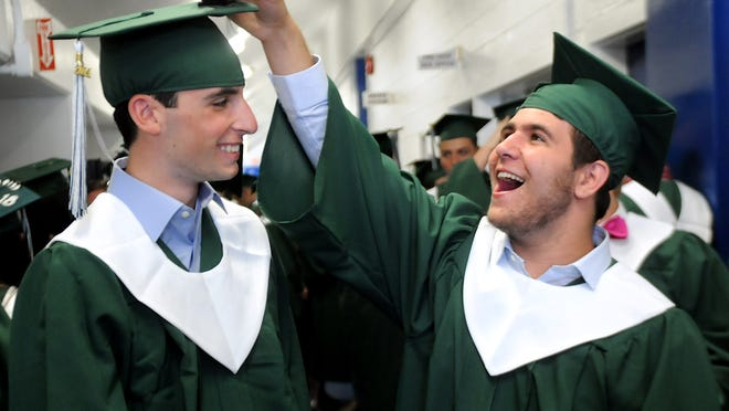 Spackenkill High School graduate Jonathan Ciago, left, gets his cap-mounted GoPro video camera adjusted by fellow graduate Nicky Citera as the procession line forms during commencement Saturday evening at the Mid-Hudson Civic Center in Poughkeepsie.
