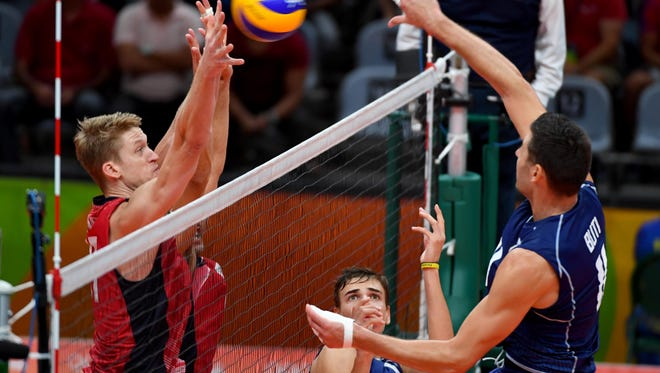United States middle blocker Maxwell Holt (17) attempts to block a spike by Italy middle blocker Simone Buti (11) in a men's semifinals volleyball match between Italy and USA at Maracanazinho during the Rio 2016 Summer Olympic Games.