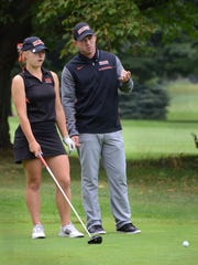 Brighton All-State golfer Annie Pietila gets advice from coach Paul Parsell before taking a shot.