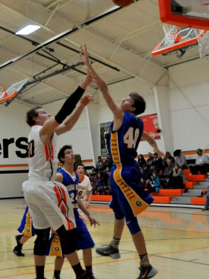 Oliver Schultz, of Capitan, makes a layup as the SonBlazers' Alex Rigg attempts the block.