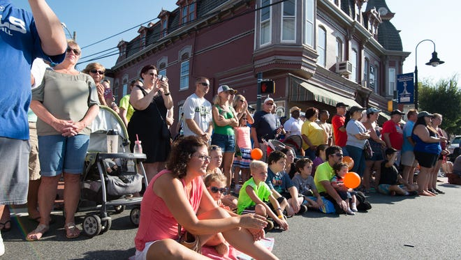 Festival goers watch the morning parade at the Middletown Peach Festival.