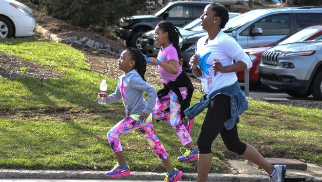 Tramaine Mills and Makyla and Mariah Jeffries near the finish at the Get Your Rear in Gear 5K race in 2015 sponsored by Asheville Gastroenterology to raise awareness and funds to fight colorectal cancer.