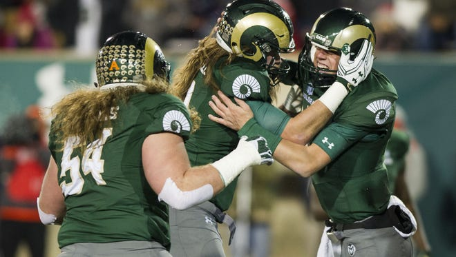 CSU quarterback Nick Stevens, left, celebrates with teammates Fred Zerblis, left and Dalton Fackrell after scoring a touchdown in the first quarter of Saturday night's win over New Mexico at Hughes Stadium. The Rams became bowl-eligible for the fourth straight year with the victory and will learn Dec. 4 which bowl game they're in.