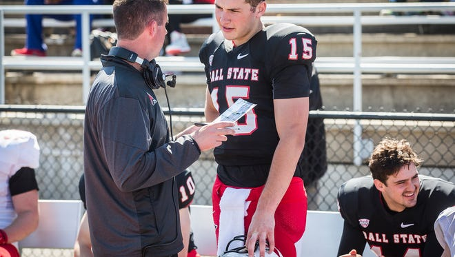 Ball State's Riley Neal chats with a coach on the sideline during the team's Spring game at Scheumann Stadium Saturday.