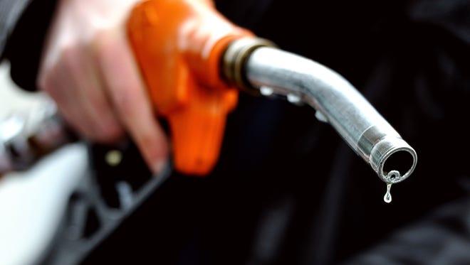 A motorist refuels at a gas pump.