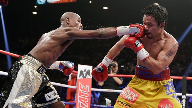 Floyd Mayweather Jr. lands a blow to Manny Pacquiao during their welterweight title fight on Saturday.