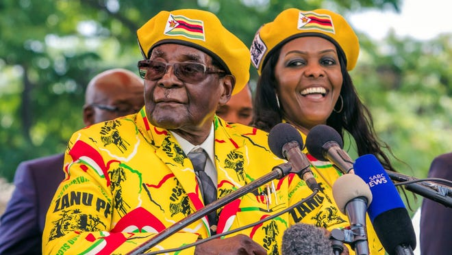 This photo taken Nov. 8, 2017, shows  Zimbabwe's President Robert Mugabe, left, addressing party members and supporters  to show support to Grace Mugabe, right, becoming the party's next vice president after the dismissal of Emerson Mnangagwa. Several tanks were seen moving near the Zimbabwean capital Harare on Nov. 14, 2017.