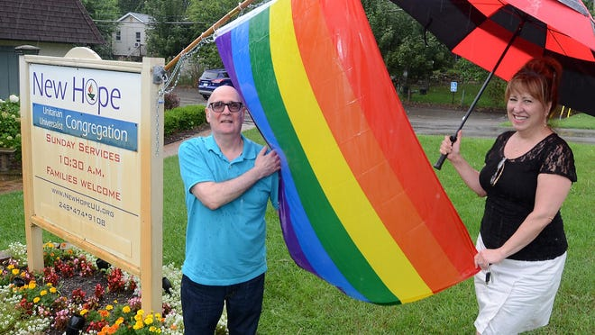 Lyon Township New Hope Unitarian-Universalist Church members Mike Kelleher and Debby Tyler stand outside the Grand River Avenue church and display its rainbow flag. The church is welcoming of all people and has had its flag stolen five times over the years.