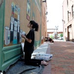 Lenise Sunnenberg and Curtis Goldstein work Thursday on the murals along the walkway between the Courthouse Square and the Canal Market District.