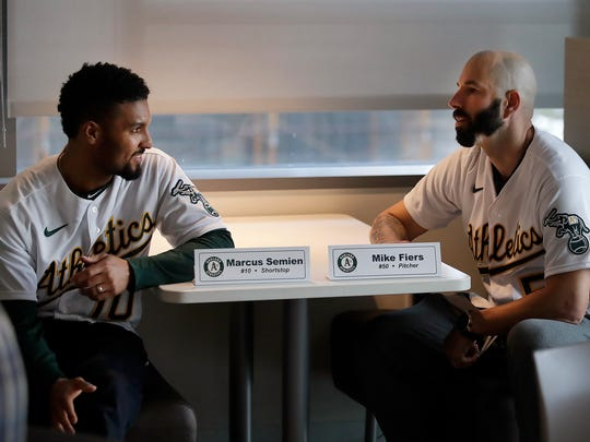 Oakland Athletics pitcher Mike Fiers, right, speaks with shortstop Marcus Semien prior to an interview with the media on Jan. 24, 2020, in Oakland, Calif. Fiers, the Oakland pitcher and whistleblower in the Houston Astros sign-stealing scandal, appeared with teammates and manager Bob Melvin at team offices.