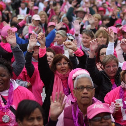 Breast cancer survivors gather in front of the stage