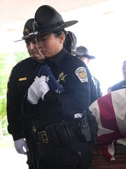Detective Juvan Chau holds a flag in front of the Anderson County Sheriff's Honor Guard carrying a casket with Master Deputy Devin Hodges, Anderson County Sheriff's Office, at the Civic Center of Anderson on Tuesday.