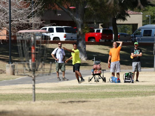 A group of disc golfers watch as a shot carries toward a basket at Vista del Camino park in Scottsdale.