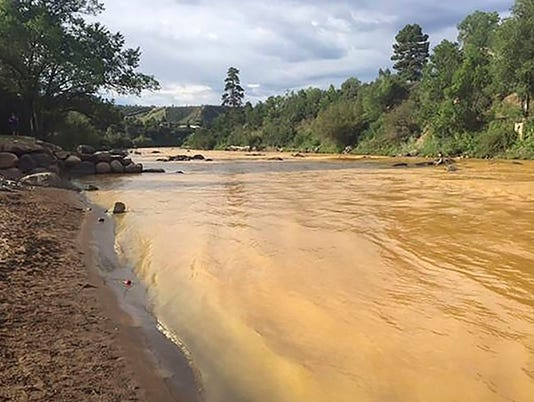 Yellow waste water that had been held behind a barrier near an abandoned mine is seen in the Animas River in Durango, Colorado