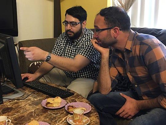 Riad Sbai of PCs for Refugees (left) shows Firas Kharma,