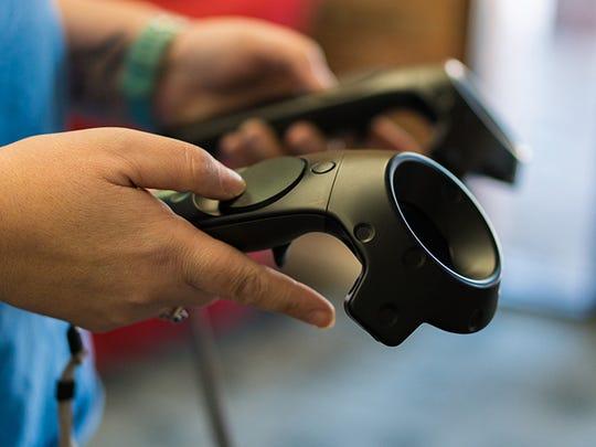 Tawn Makela, co-owner of VR Junkies arcade, demonstrates