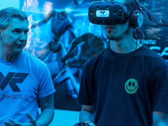"Chris Krakowsk (left), co-owner of VR Junkies in Tempe, explains to Tyler Powell how to play ""Arizona Sunshine,"" a post-apocalyptic VR zombie shooter game."