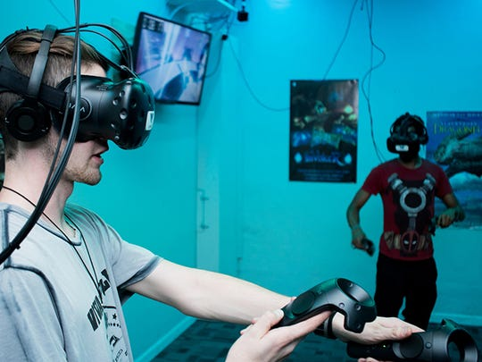 "Jack Fortin (left) and Stefan Hussey battled each other in the virtual reality game ""Skyfront"" during their first time at the arcade."