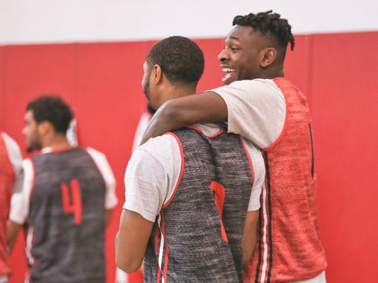 """Louisville players V.J. King, left, and Lance Thomas walk into a practice Wednesday afternoon at the YUM! practice facility. """"I don't think we could've made a better interim (AD) hire than Vince (Tyra),"""" said David Padgett at a press conference earlier. """"He and I are both in tough positions."""""""