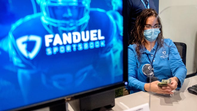 Cashier Tammy McGinnis counts the cash from a recent bettor at the new FanDuel betting facility that opened Thursday, Sept. 10, 2020 at the Par-A-Dice Casino in East Peoria. The in-person sportsbook opened in conjunction with the release of an app for FanDuel's online sports betting service in partnership with Boyd Gaming, the owners of the Par-A-Dice.