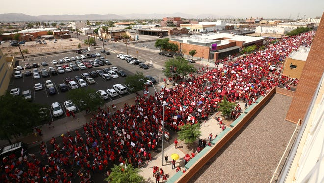 Arizona teachers march to the Arizona State Capitol during a walkout for higher pay and more education funding on April 26, 2018 in Phoenix.