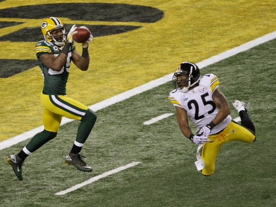 Green Bay wide receiver Greg Jennings hauls in a 21-yard touchdown pass in the first half. The Steelers' Ryan Clark barely misses deflecting the hard pass from quarterback Aaron Rodgers