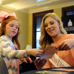 """Miss University of Southern Mississippi Hannah Roberts autographs a picture for Carlyn Underwood during the """"Princesses for Pages"""" event Sunday at the Ogletree House. Roberts' 10-year project """"Pages of Love"""" collects new and gently used books that are donated to hospitals, medical and dental clinics and other organizations for children to read and take home."""