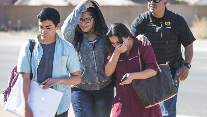 Crying students leave a bus that took them away from Independence High School Friday morning after two students were shot and the campus was locked down.