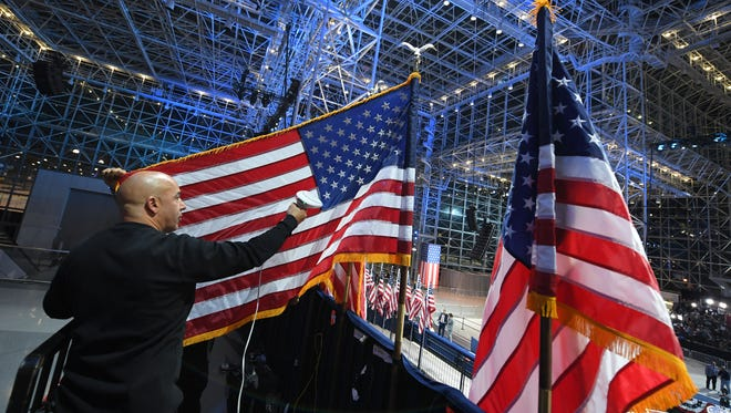 A worker sreams a US flag at the Jacob K. Javits Convention Center in New York on November 8, 2016 where Democratic presidential candidate Hillary Clinton's election night event is held.