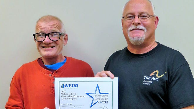 Arc of Chemung client Gary Soule, left, with mobile work crew manager Tom Harrigan, shows off the award he received from New York State Industries for the Disabled.
