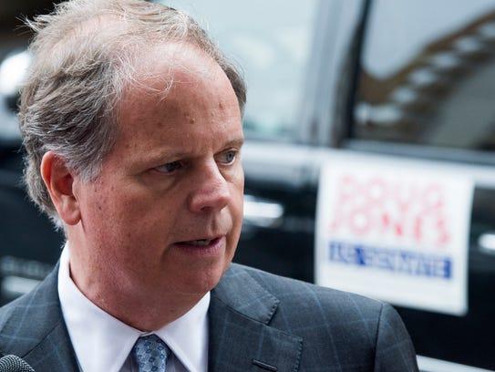 U.S. Senate candidate Doug Jones talks with the media