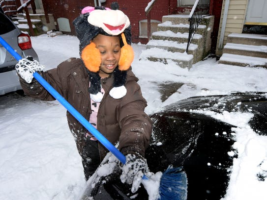 Azaria Ray, 8, of York City, clears snow from her mother's