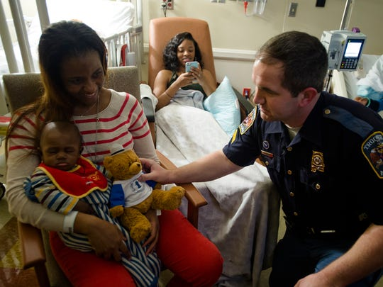 Corp. Jess Thornton, Alabama State Trooper, hands a teddy bear to Amir Cody, four-month-old, as his mother Kristen Cody holds him on Tuesday, Dec. 22, 2015, at Baptist Medical Center East in Montgomery, Ala.