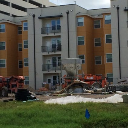 Construction equipment sits close to the Plaza on University apartment complex.
