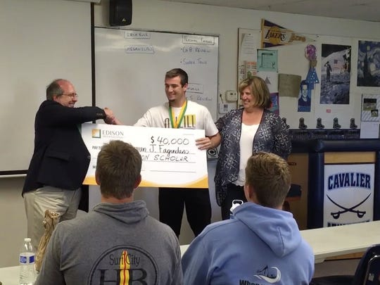 Southern California Edison's Local Public Affairs Region Manager Brian Thoburn, left, presents an oversized check to Darren Fagundes, center, for a $40,000 Edison International scholarship. Christine Fagundes, Brian's mother, right, looks on.