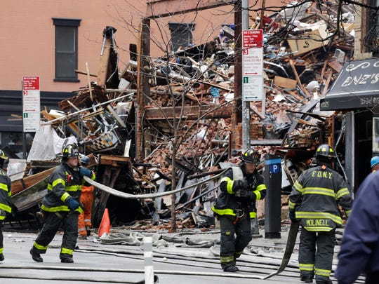 Firefighters roll up fire hoses at the site of an explosion and fire in the East Village neighborhood of New York on Friday. Authorities say two people are unaccounted for following an apparent gas explosion that leveled three buildings. Preliminary evidence suggested a gas explosion amid plumbing and gas work inside the building was to blame.