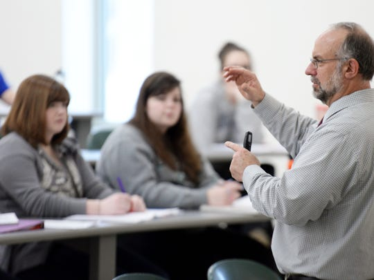 UW-Green Bay associate professor of natural and applied sciences Steven Meyer conducts a lecture class on weather Wednesday in Mary Ann Cofrin Hall. Meyer is one of 158 campus employees who were offered early retirement packages as part of the university's effort to cut costs.