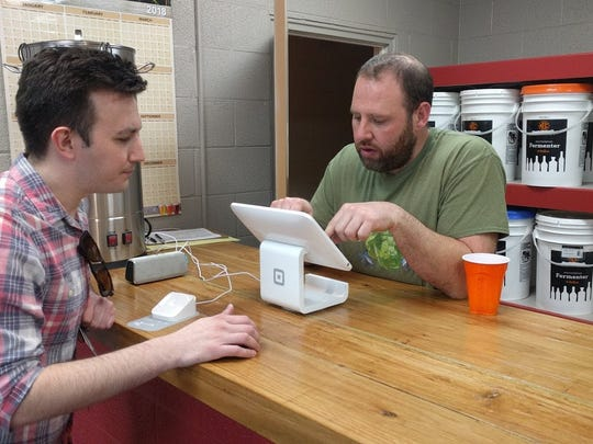 Peter Fallon, right, helps a customer at his new homebrew shop in Pendleton.