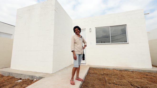 Community activist Maria Da Penha Macena stands in front of one the new houses built by the city of Rio during a tour of Vila Autodromo near the Olympic Park on July 30.